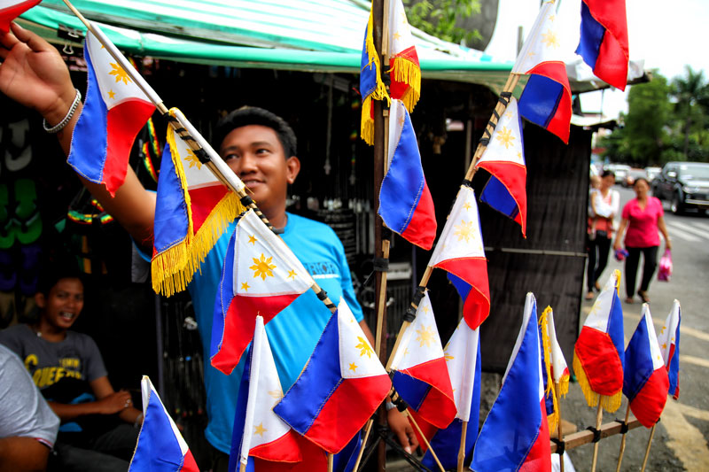 "ON SALE.  A vendor sells miniature Philippine flags along Davao City's San Pedro Street.  On Wednesday, the country celebrates the 115th Independence Day.  However, militant umbrella organization Bayan said ""Under the Aquino regime, we have a lethal combination of sham independence and sham development.  Despite the repeated claims of economic growth, our people remain mired in crisis…created by our lack of economic sovereignty.""  (davaotoday.com photo by Ace R. Morandante)"