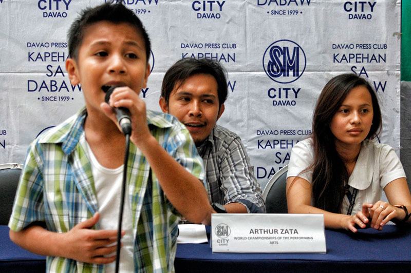 SHOWCASING WORLD-CLASS TALENT.  Lloyd Montebon, 11, of Angliongto village in Davao City belts out a song during Monday's SM Kapehan.  He's one of the 30 Mindanaoans who are hoping to bag a gold medal from the World Championships of Performing Arts competition in Hollywood, USA.  Behind him are Director Arthur Zata (left) and fellow qualifier Jizelle Dea Formilleza.  (davaotoday.com photo by Medel V. Hernani)