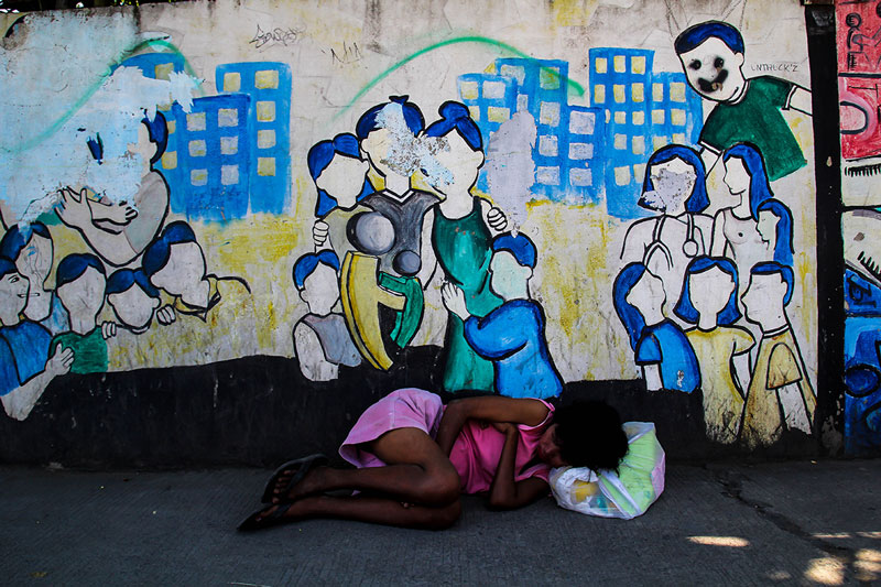 """CONTRAST.  Despite the Aquino government's declaration of """"great economic success"""" with the supposed 7.8 percent growth rate of the country's Gross Domestic Product, many Filipinos are still living like her: homeless and begging for basic needs.  (davaotoday.com photo by Ace R. Morandante)"""