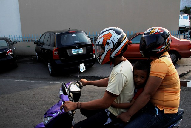 Despite the city's strict helmet rules for motorcycle riders, some incidents such as this family allowing a kid to ride without his helmet slipped past traffic management personnel that police the streets. (davaotoday.com photo by Medel V. Hernani)