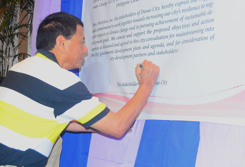 MAYOR'S SIGNATURE Davao City Mayor Rodrigo Duterte signs the city's commitment to climate change action in Tuesday's consultation with the United Nation's Habitat for Climate Change Adaptation at the Pinnacle Hotel. The consultation was attended by government and business sectors to discuss on the city's action on climate change. (davaotoday.com photo by Earl O. Condeza)