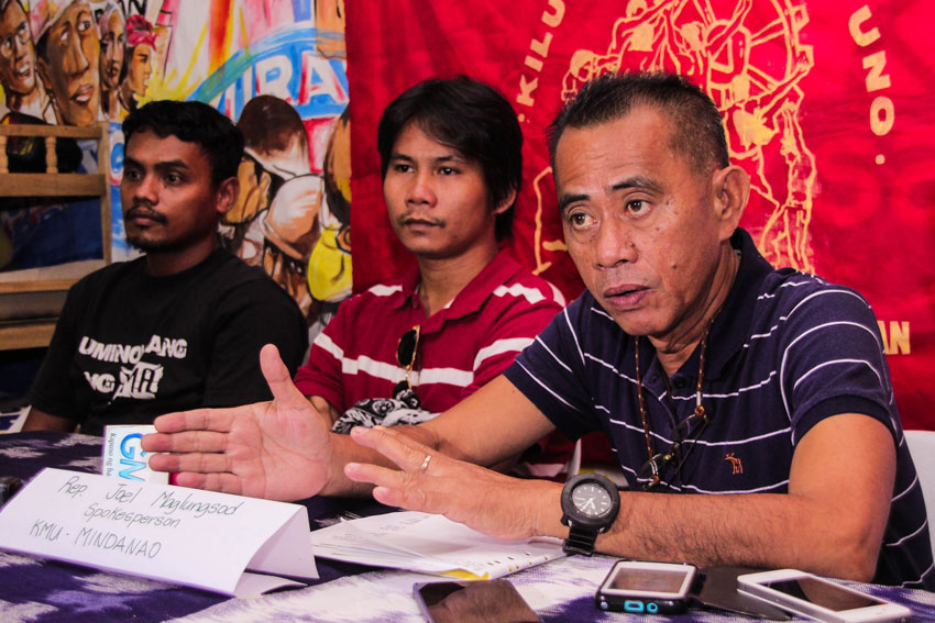 Joel Maglunsod (right) of the labor group Kilusang Mayo Uno joins workers of Superstar Coconut Products in demanding the Department of Labor to enforce occupational safety standards following the factory accident that killed one worker.