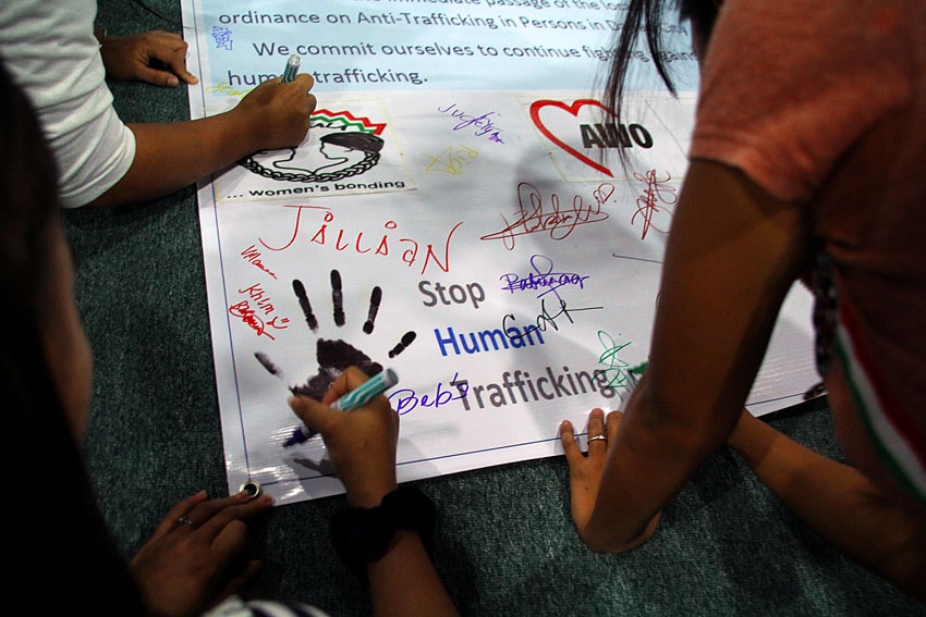 Victims of human trafficking and their supporters from various barangays in the city signify support to stop human trafficking by signing a unity statement Friday. (Ace R. Morandante/davaotoday.com)