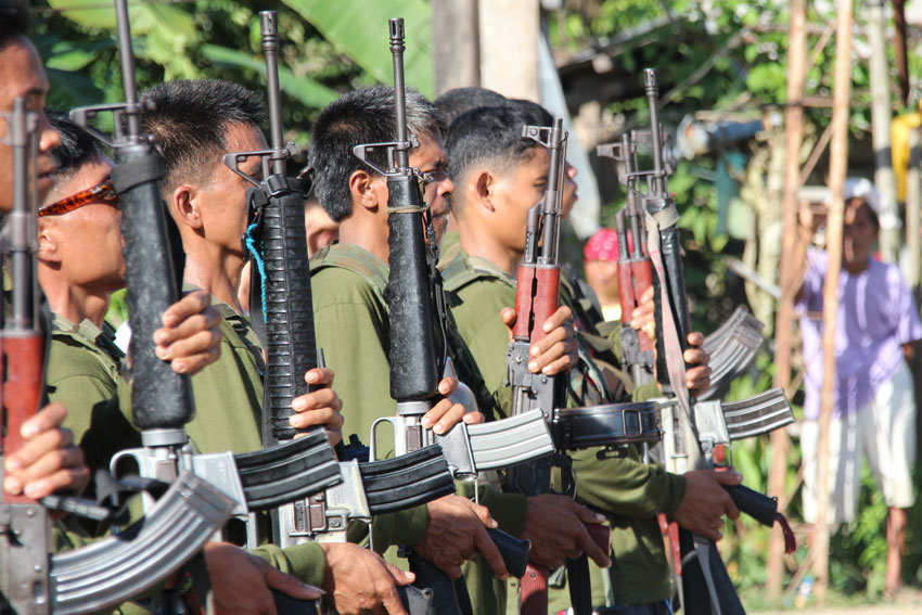 "Members of the New People's Army sing the Internationale before the release of the ""prisoners-of-war"" Cpl. Benjamin Samano and Pfc. Alvin Ricarte. (Johannes Realista Garado/davaotoday.com"