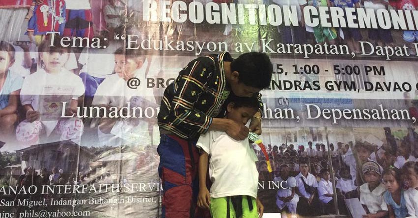 Crispin Subla pins the ribbons to son, Miguel who will be entering Grade 1 this school year during the moving-up ceremony of Misfi Academy held here on Monday. 52 students had to travel for several hours just to attend their recognition rites allegedly because a paramilitary group refuses the school's operation. (Photo contributed by Glades Jane Maglunsod)