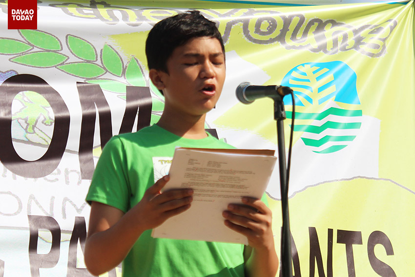 Jirojunn Juri Lopoz, Supreme Pupil Government Federation President of Davao Central District, reads his message on stage before the tree planting activity in Barangay Tigatto, Buhangin, Davao City, on Wednesday morning. (Medel V. Hernani/davaotoday.com)