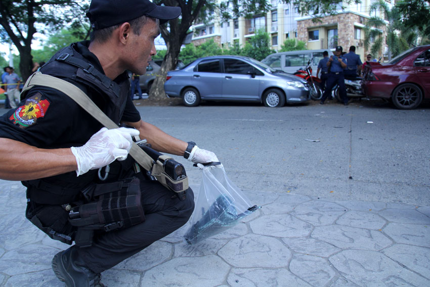 FRAGMENTS. A swat officer collects fragments as evidence from the bomb explosion in the passenger van which exploded in Ecoland, Davao City Wednesday morning. (Ace R. Morandante/davaotoday.com)