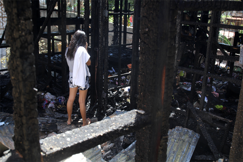 Rainbe Bartolome, a 17-year-old college student, stares at the remains of her dormitory. A new boarder, she says all her possessions, including her books, were burned. (Photo by Ace Morandante/davaotoday.com)
