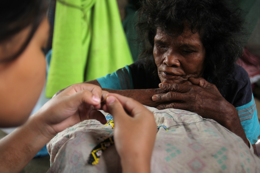 HALF BLIND. A Manobo elder from Talaingod, Davao del Norte observes a volunteer trying her bead work inside an evacuation center in a church-owned compound in Davao City. The old woman still manages to make a traditional handicraft despite her half-blindness. (Ace R. Morandante/davaotoday.com)