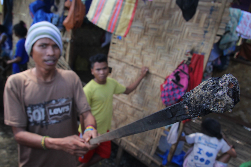A Lumad shows the torch that was used to burn the UCCP Haran evacuation shelter. (Photo by Ace Morandante/davaotoday.com)