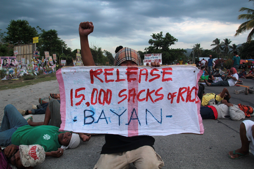 RAISED FIST. An activist raises his fist while holding a streamer with the demand for 15,000 sacks of rice. Behind him are farmers sprawled in the national highway of Koronadal-Gen.San. (Ace R. Morandante/davaotoday.com)