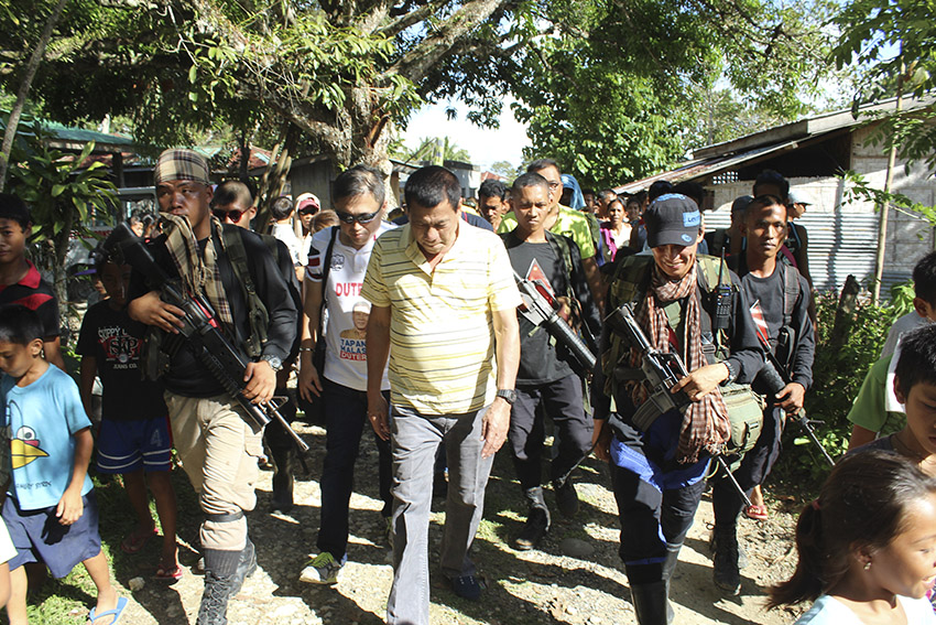 ESCORT. Members of the NPA escorted Duterte as he walks toward the gymnasium in Barangay Lumiad, Paquibato. (Earl O. Condeza/davaotoday.com)