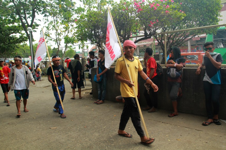 Workers hold the flag of party-list Anakpawis, while waiting to start the march.