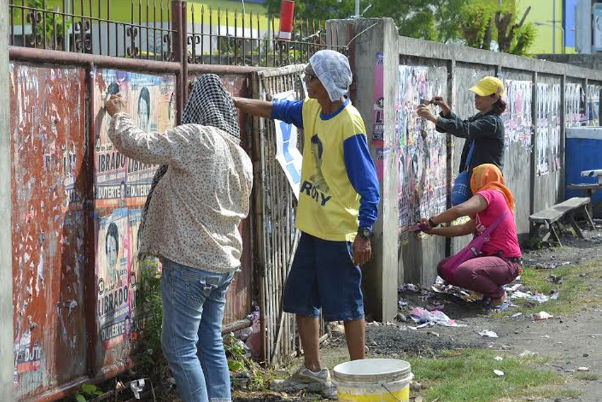CLEANING UP. Three days after the national and local elections, supporters of a candidate tear down campaign posters along Quimpo Boulevard, Davao City.(Ace R. Morandante/davaotoday.com)