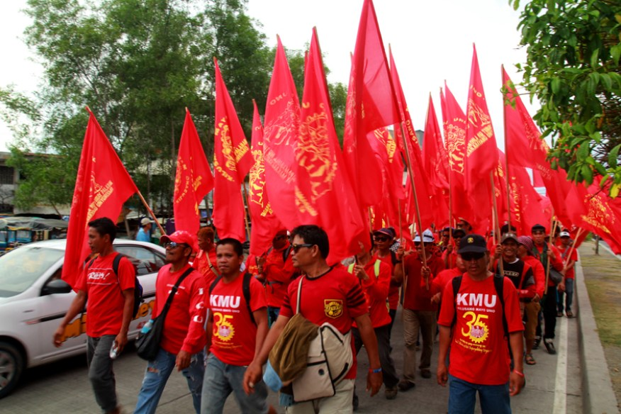 Union members affiliated to the labor center, Kilusang Mayo Uno raise the red flags while they march the streets from Magsaysay Park to Rizal Park.