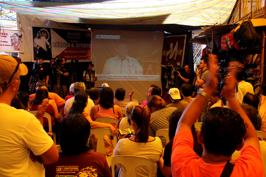 Davaoeños cheer and applaud President Rodrigo Duterte as they watch him deliver his inaugural speech through a big screen monitor inside the Mallengke in Bankerohan Public Market in Davao City on Thursday, June 30.(Ace R.Morandante/davaotoday.com)