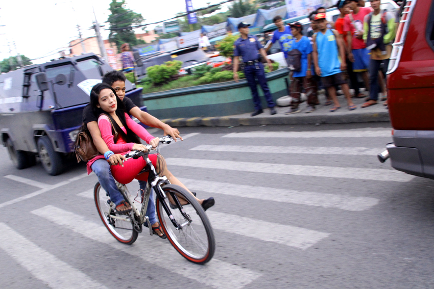 A couple rides in a bike without any protection along Quimpo Boulevard in Davao City. (Ace R. Morandante/davaotoday.com)