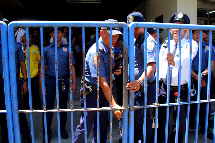 Members of the Davao City Police Office temporarily lock the gate of the Hall of Justice because of the rally staged by protesters on Wednesday, June 29. The protesters condemn the warrant of arrest for 15 activists on alleged kidnapping and serious illegal detention of the indigenous people evacuees in a church compound in Davao City. (Ace R. Morandante/davaotoday.com)