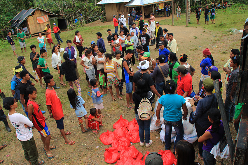 RELIEF DISTRUBUTION. Volunteers from various organizations from Monkayo, Compostela Valley and Davao City distribute 50 packs of relief goods to residents affected by the armed encounter in Barangay Rizal, Monkayo, Compostela Valley. (Earl O. Condeza/davaotoday.com)