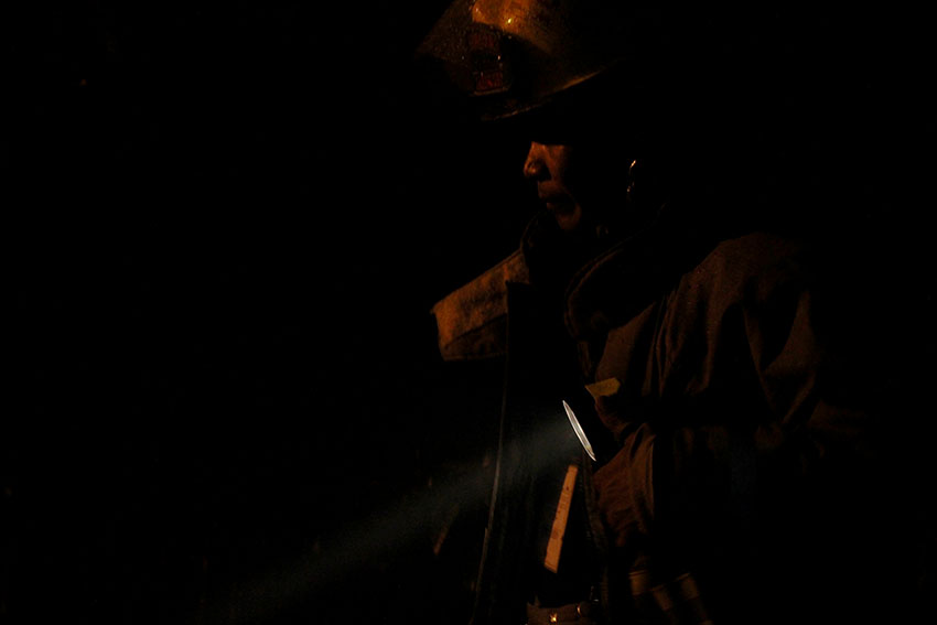 FIREMAN. A fireman uses his flashlight to inspect a burned house in Pag-asa Village, Matina Aplaya, Davao City on Wednesday afternoon, August 10, 2016.  Five houses were razed in the fire. (Paulo C. Rizal/davaotoday.com)