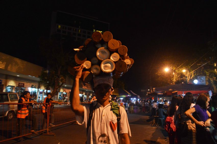 A man tries his luck selling bamboo coin banks in Roxas night market. (Medel V. Hernani/davaotoday.com)