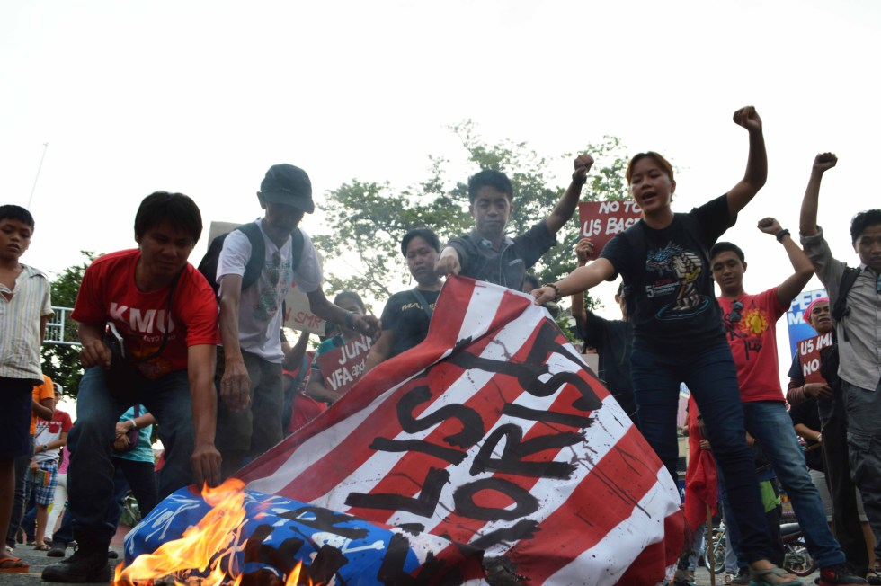"Protesters shout ""US imperialist No. 1 terrorist"" as they burn a US flag in a rally in Davao City on Sunday, September 11, 2016."