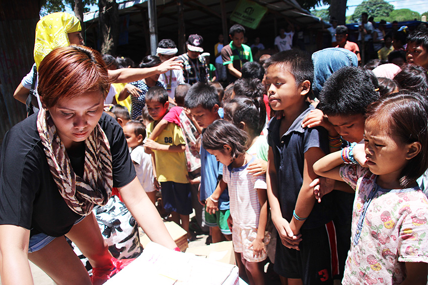 DONATIONS. Manobo children receive school supplies from the Youth for Development, represented by Willariza Veloso Tigle on September 22, Thursday morning. (Paulo C. Rizal/davaotoday.com)