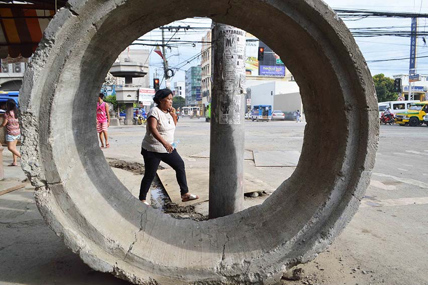 A woman streches her feet while walking across the corner of Magallanes and Torres Street, Davao City, which undergo road improvement. (Medel V. Hernani/davaotoday.com)
