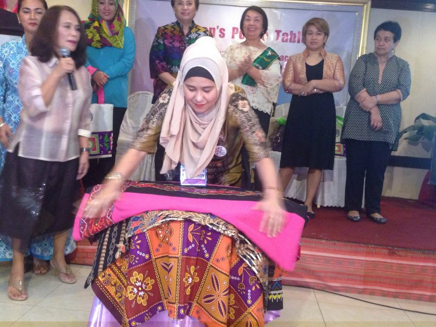 A woman participant to the opening of the Women's Peace Table lays a the traditional cloth to signify the unity of women in Mindanao to actively participate in the peace process. The opening was held at the Royal Mandaya Hotel in Davao City on Monday, Nov. 28. (Zea Io Ming C. Capistrano/davaotoday.com)