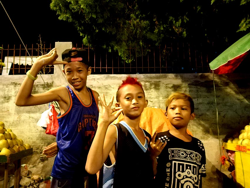 ROXAS CAROLLERS. From left to right: Yuko, 14; Inggo, 12; and CG, 12 pose for the camera while taking a break from caroling in Roxas Avenue, Davao City on Wednesday, Dec. 21. (Paulo C. Rizal/davaotoday.com)