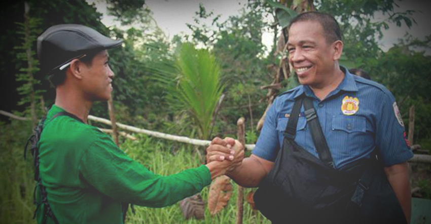 MOMENT OF PEACE. A member of the New People's Army and a police escort shake hands as they meet during the NPAs release of its captured soldiers in San Luis, Agusan del Sur in May 2016. The photo was taken by Ace Morandante and was awarded during the Globe Media Excellence Awards in 2016. (davaotoday.com file photo)
