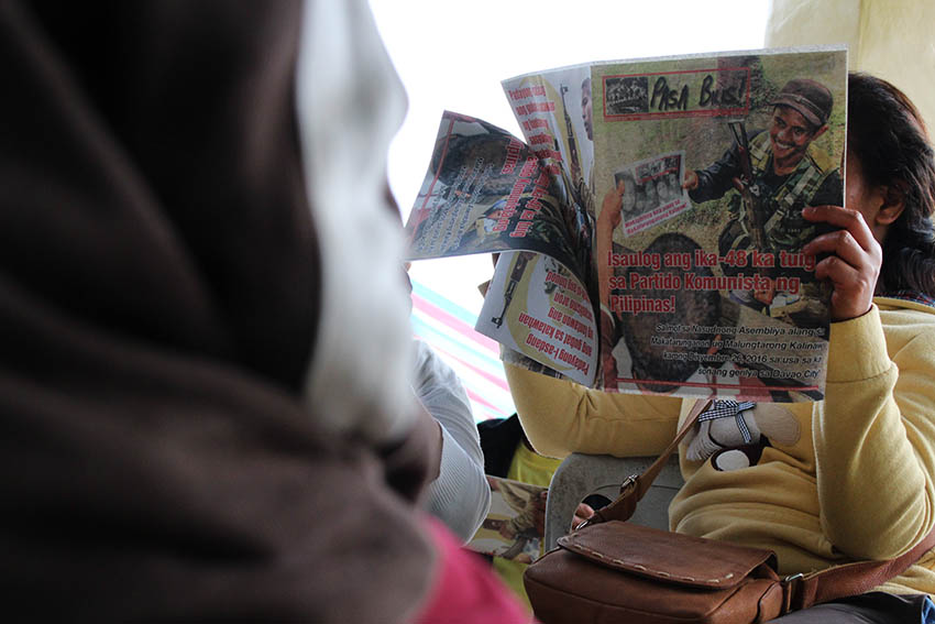 A local resident reads the communist publication Pasa Bilis! (Pass it Quickly) during a peace forum organized by the National Democratic Front in Barangay Makopa, Laak, Compostela Valley on Tuesday, Jan. 10. (Paulo C. Rizal/davaotoday.com)