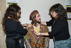 Costume Supervisor Stacie Logue makes some final adjustments to tenor Tim Petty's costume.