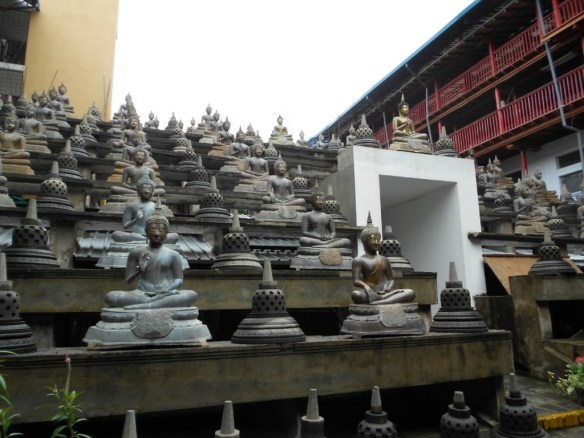Buddha statues not far from a cat-sized rat scurrying about.