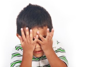 Scared toddler covering his face