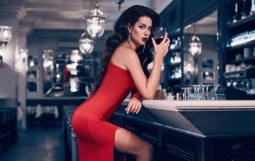 Gorgeous young brunette woman in red dress with wine