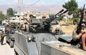 جنود الجيش اللبناني يقودوا ناقلات الجنود المدرعة في بلدة عرسال شمال لبنان على الحدود مع سوريا يوم الاربعاء. (إيه إف بي/ موقع جيتي إيميدجز)