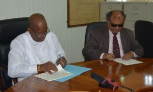 FLASH BACK: Finance Minister, Winston Jordan (left) and Fedders Lloyd's representative, Ajay Jha, signing the Memorandum of Understanding to build the Specialty Hospital