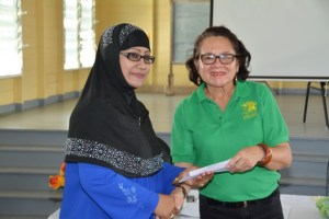 First Lady, Mrs. Sandra Granger presenting Ms. Latchmin Azeez with a letter a approval for a grant for the Bushlot-Armadale Women's Group.