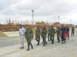 Head of the Ministry of Public Infrastructure's Special Projects Unit, Lawrence Mentis (front, left) in discussion with Guyana Defence Force Captain, Daniel Seeram, as soldiers officially join the D'Urban Park Development Project workforce