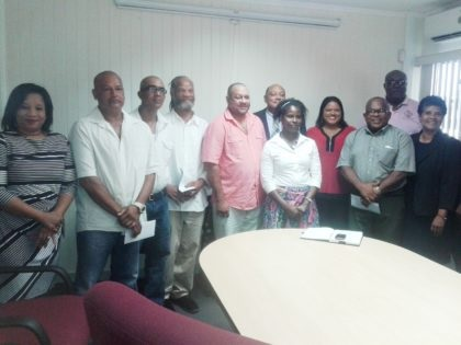 Minister of Natural Resources Raphael Trotman (back centre) with small miners who received their mining lands. Also in photo is Chairperson of the Closed Areas Committee Dela Britton (far left) and Acting Commissioner of the GGMC Newell Dennison (back row far right)