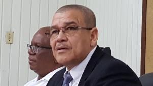 Commissioner General of the Guyana Revenue Authority (GRA), Godfrey Statia. In background is Finance Minister, Winston Jordan.