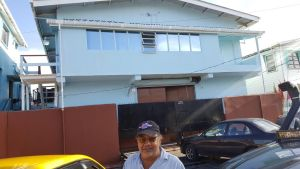 """Lawrence """"Larry"""" Singh standing in front of the bond on 29 Sussex Street, Albouystown that he is renting government."""