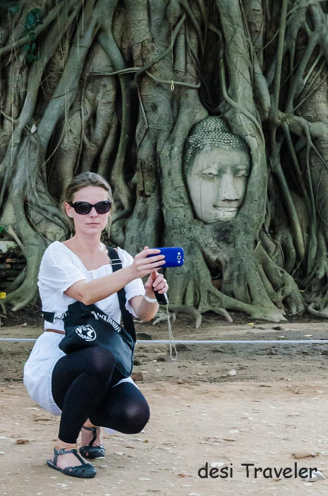 woman taking selfie with Buddha Head in Tree roots Thailan