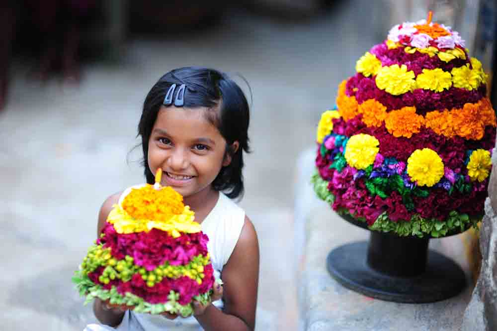 A girl with Bathukamma smiling