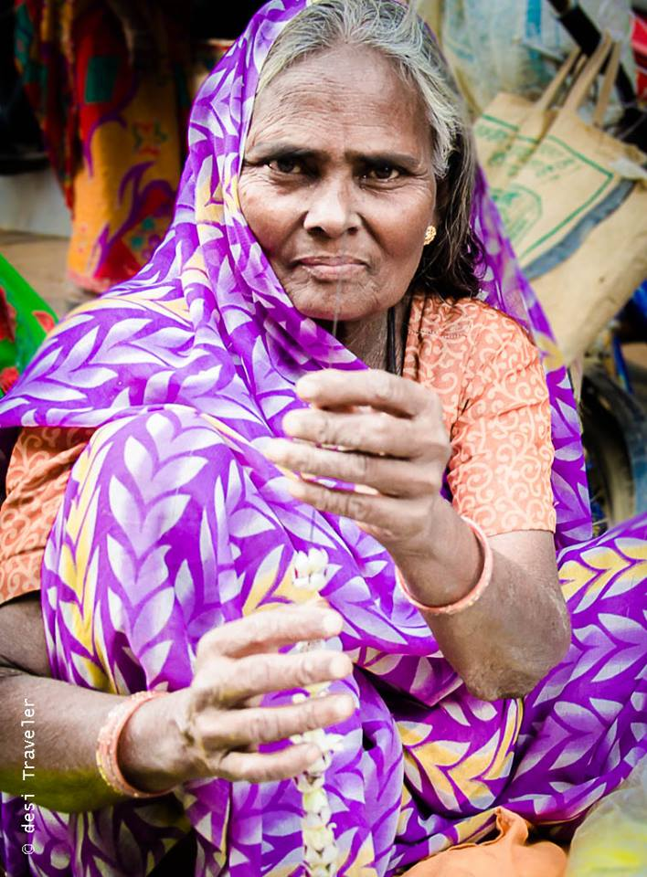 Women making garland of aak or Calotropis flowers for Shiva