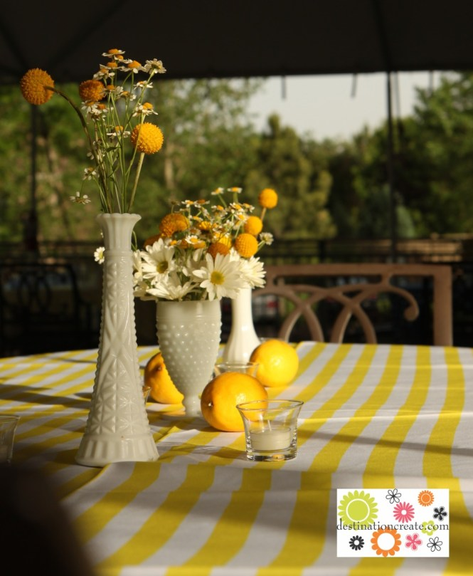 Blue and yellow wedding centerpieces in milk glass vases-white daisies, feverfew and yellow billy balls with lemons as table scatter.
