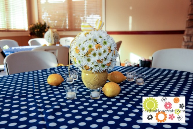 White daisy and yellow button mum flower ball centerpiece on yellow garden pot with lemons as table scatter.