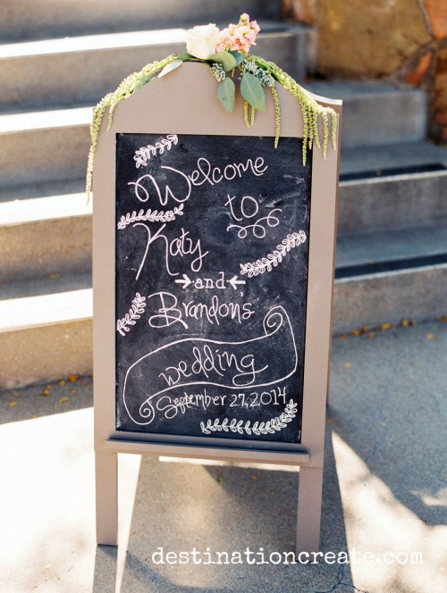 Chalkboard sign welcomes guests to romantic blush & gold wedding in Golden CO