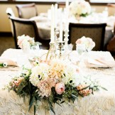 Lush, romantic centerpieces rise above champagne crinkle linens and fill the room with elegance at this gold and blush wedding in Golden Colorado held at Rolling Hills Country Club